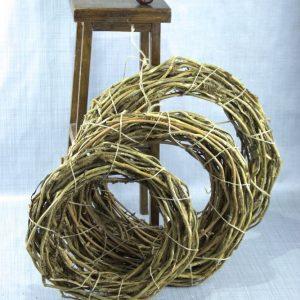 Drie kransen gemaakt van twijgen in verschillende groottes leunen tegen een houten krukje.